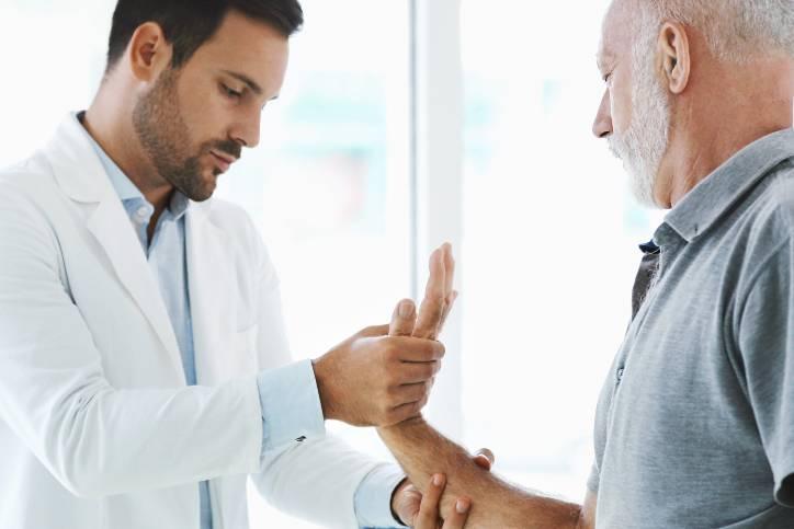 doctor working with elderly man's wrist