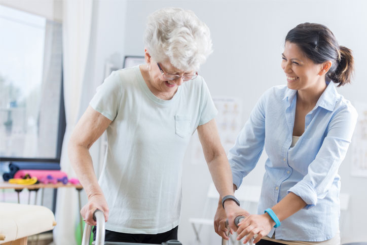 female care giver helping elderly woman practice walking after stroke