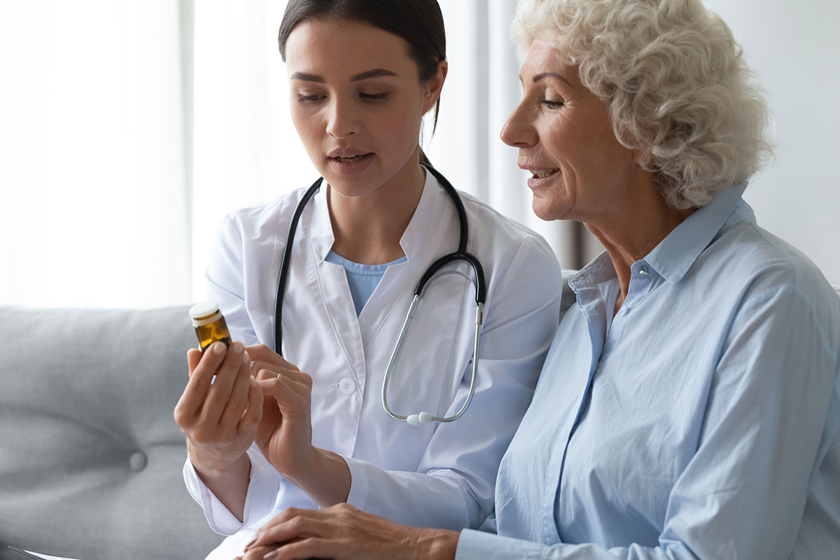 young female doctor discussing medication with elderly woman
