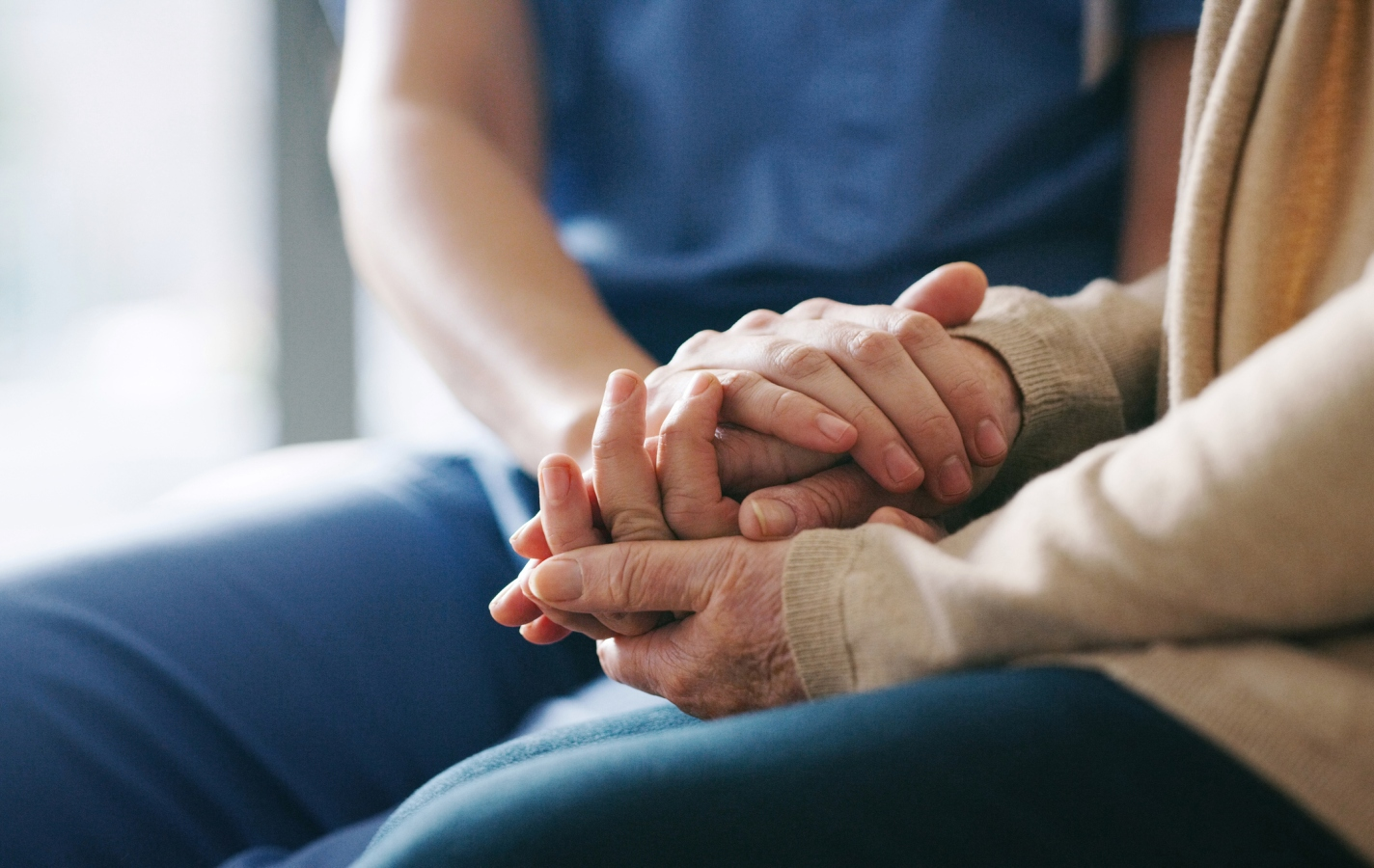 senior woman holding hands with a nurse