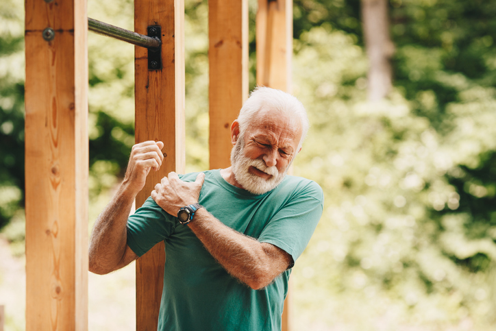 Senior man suffering with shoulder pain during workout