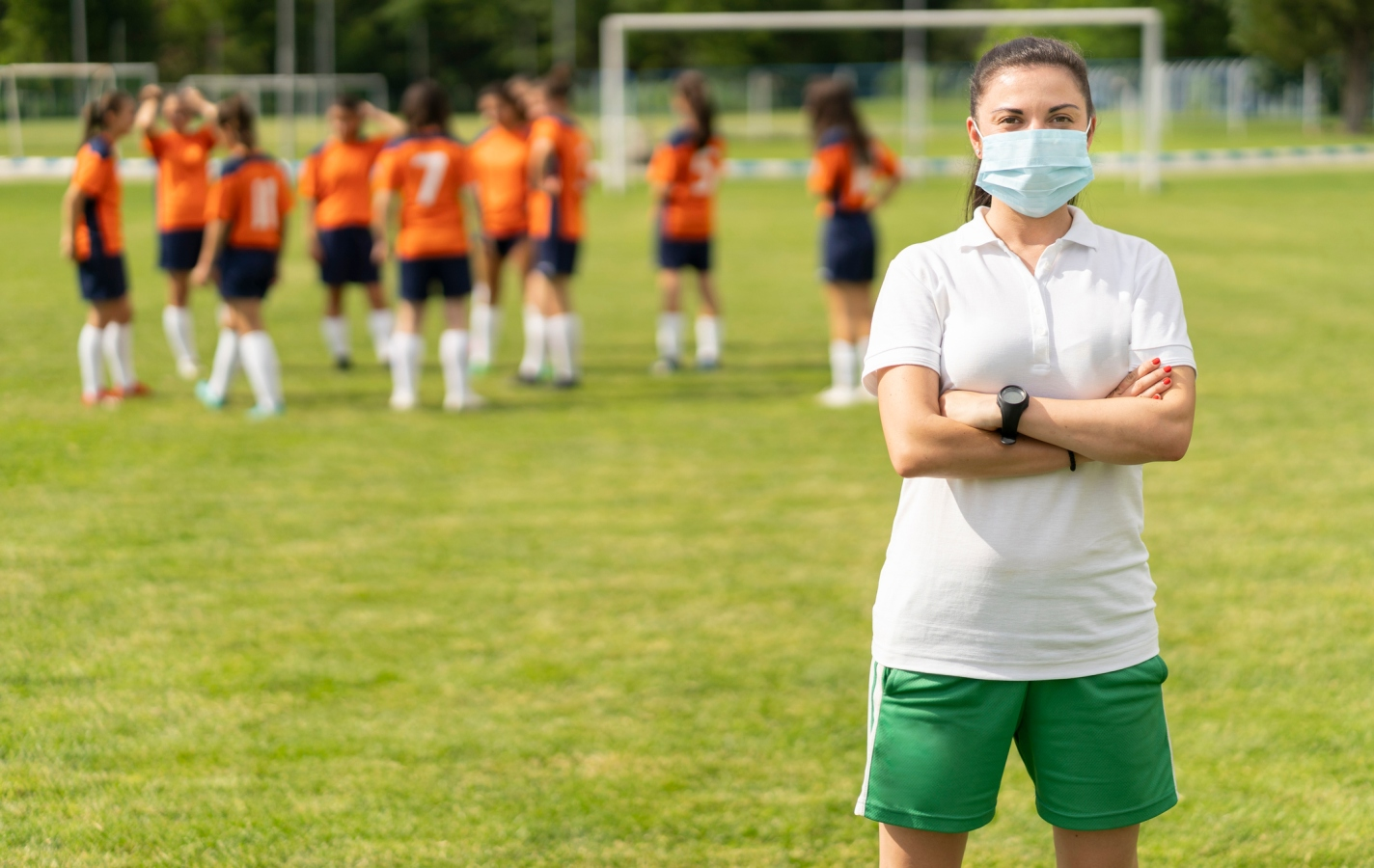 COVID-19. Portrait of a young football coach wearing face mask due to coronavirus pandemic.