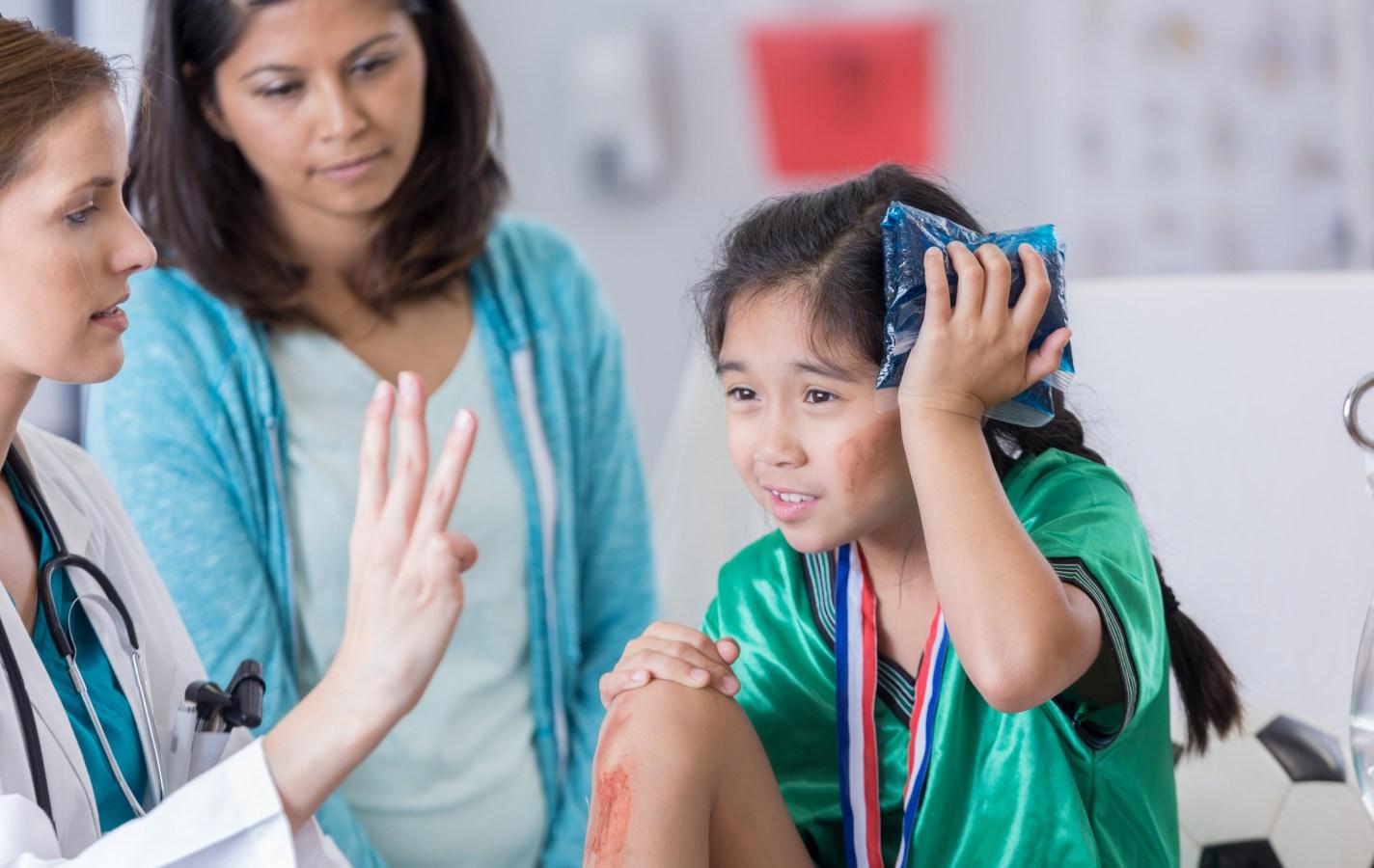 ER doctor examines dazed injured soccer player