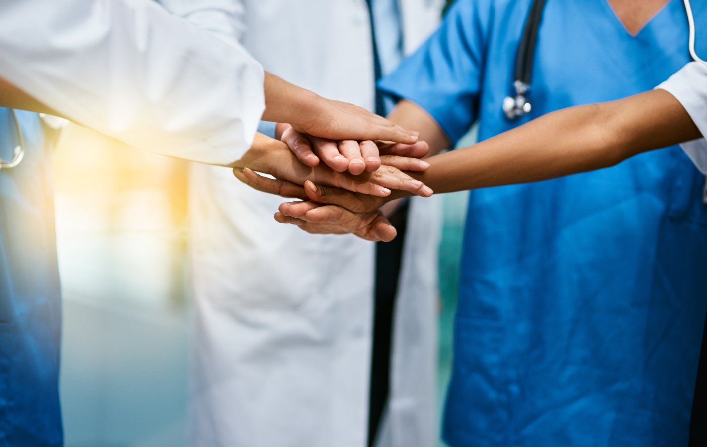 group of unrecognisable medical practitioners joining their hands together in unity