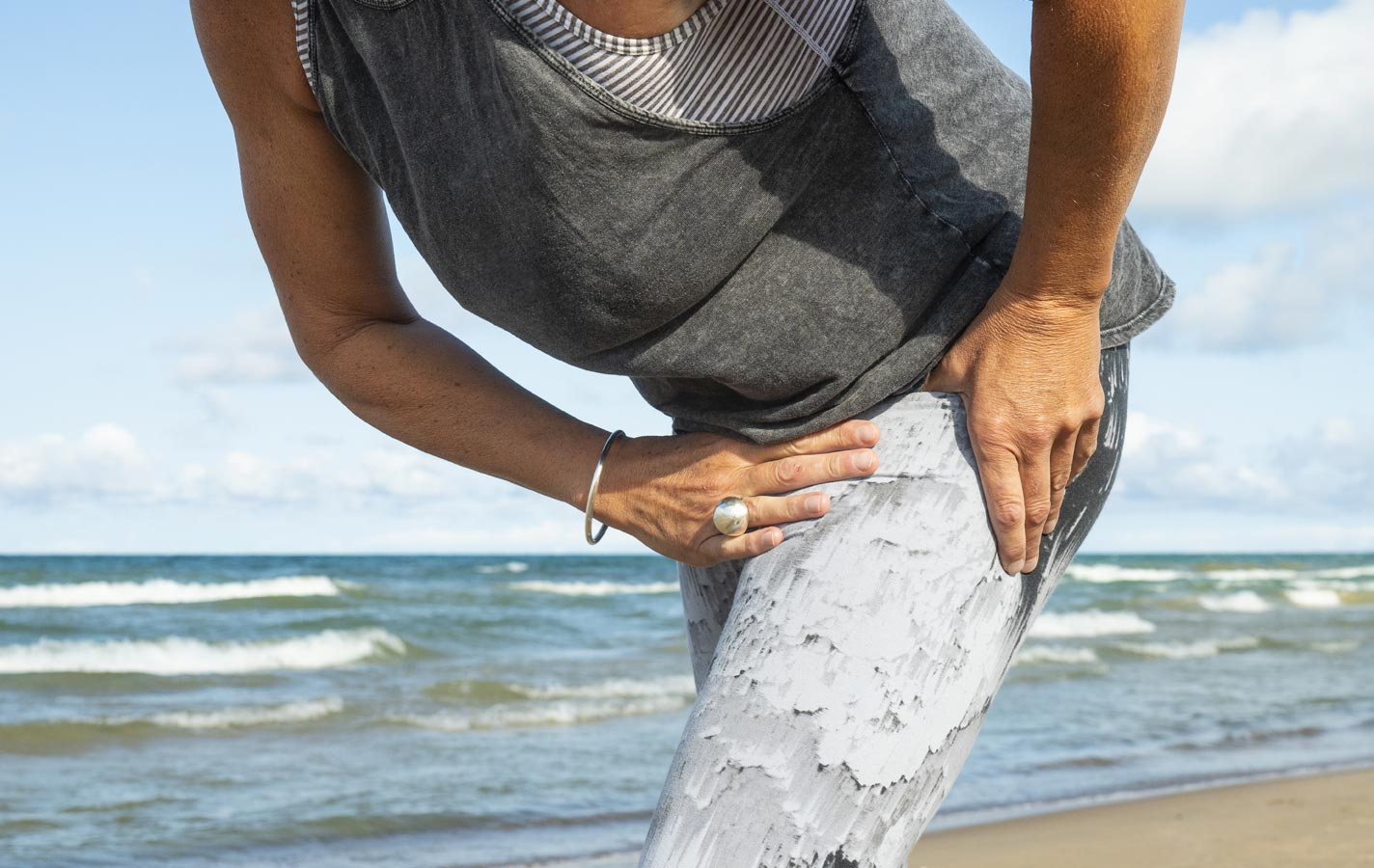 elderly woman on beach holding hip