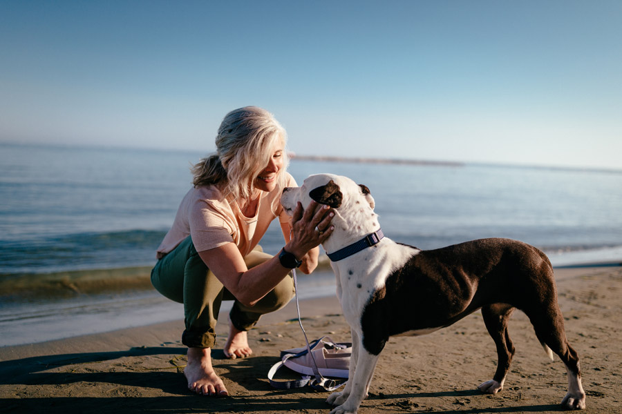 woman kneeling next to ped dog on beach