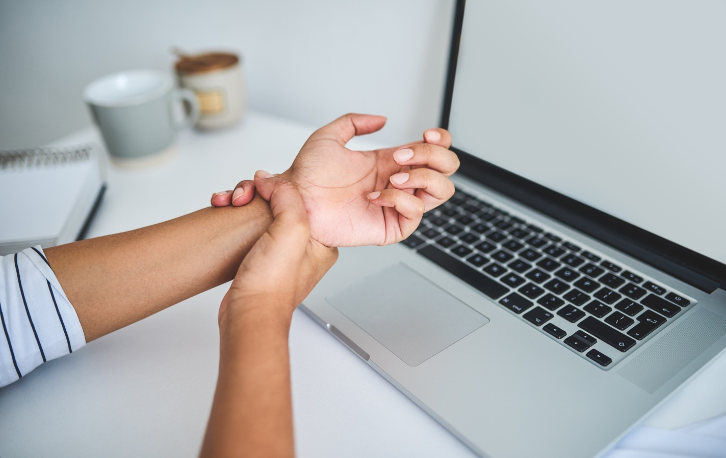 woman using laptop experiencing carpal tunnel pain in wrist