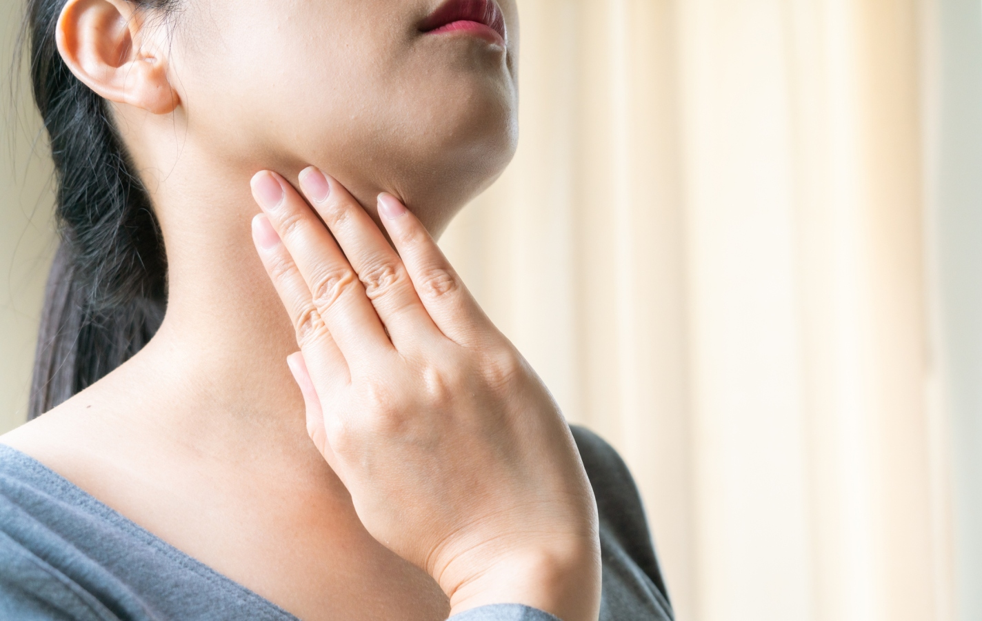 woman holding her hand to her sore throat