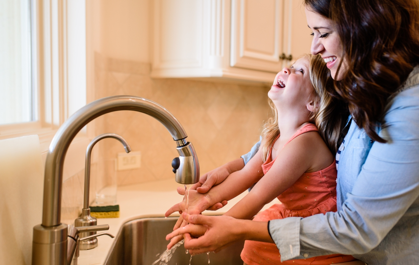 Mother and Daughter Washing Hands and Laughing