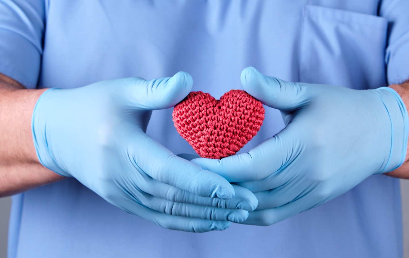 doctor with blue latex gloves holding a red heart