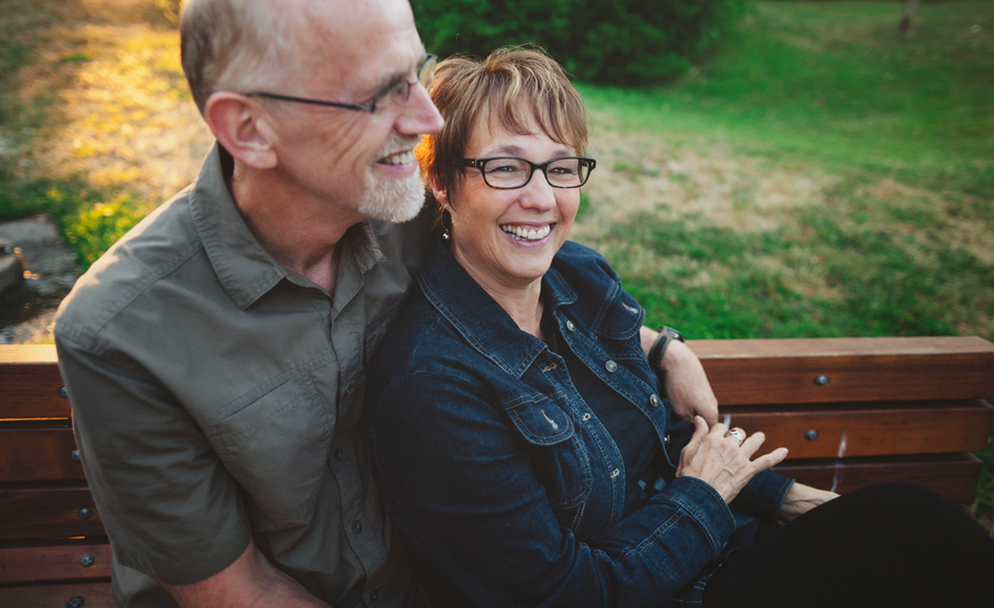 Happy Middle Aged, Retired Couple Laughing And Cuddling Outside Sitting On A Bench