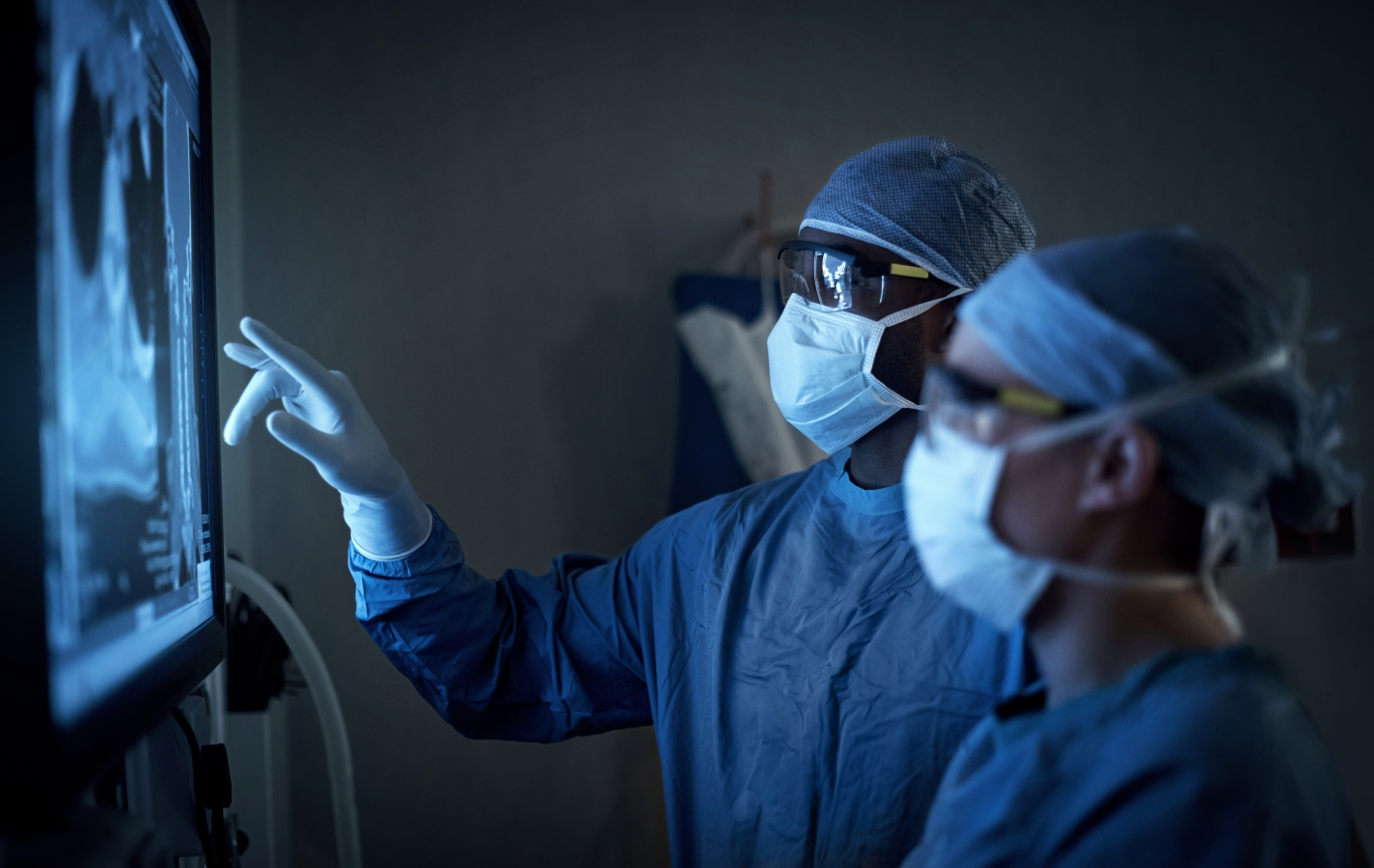 two surgeons analyzing a patient's medical scans during surgery