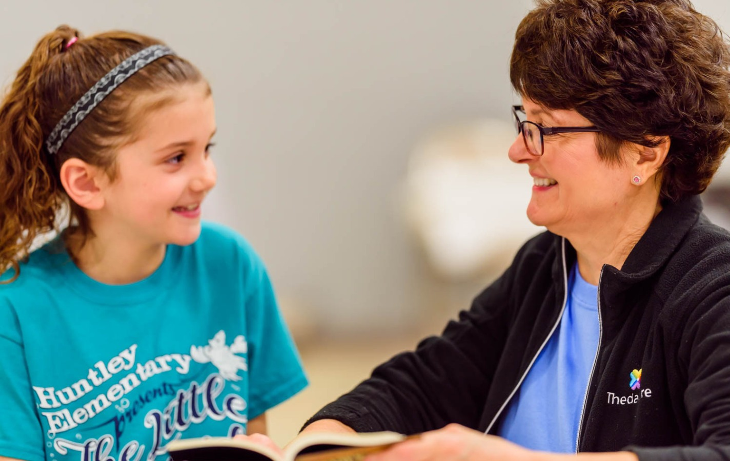 Event volunteer reading book with young girl