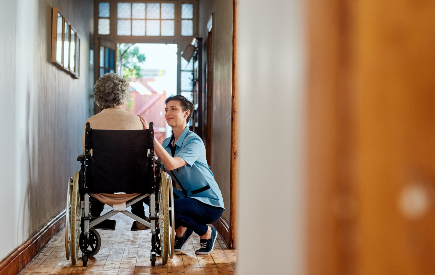 Young care giver crouching next to elderly woman in wheelchair