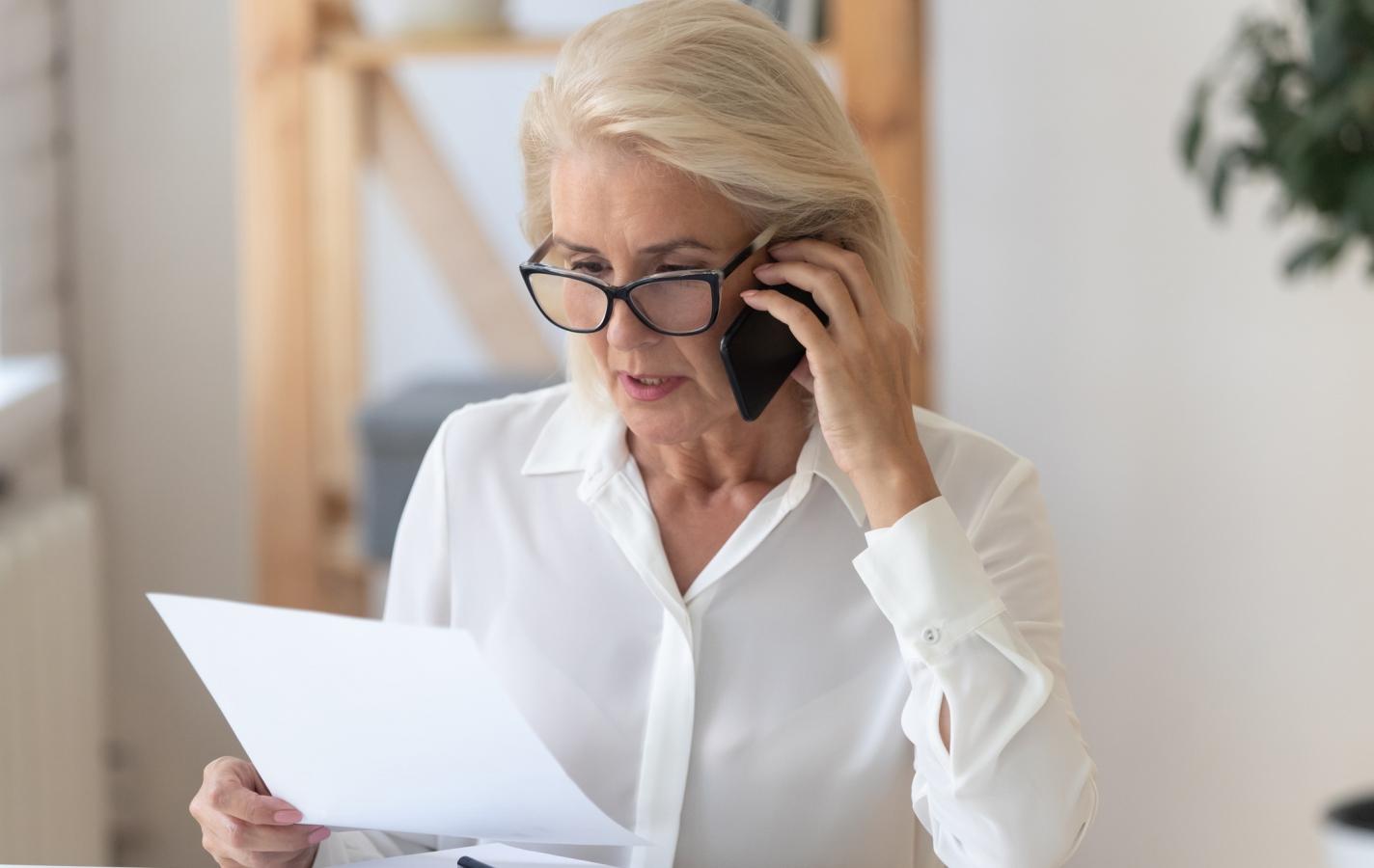 Serious senior woman talk on cellphone discussing paperwork