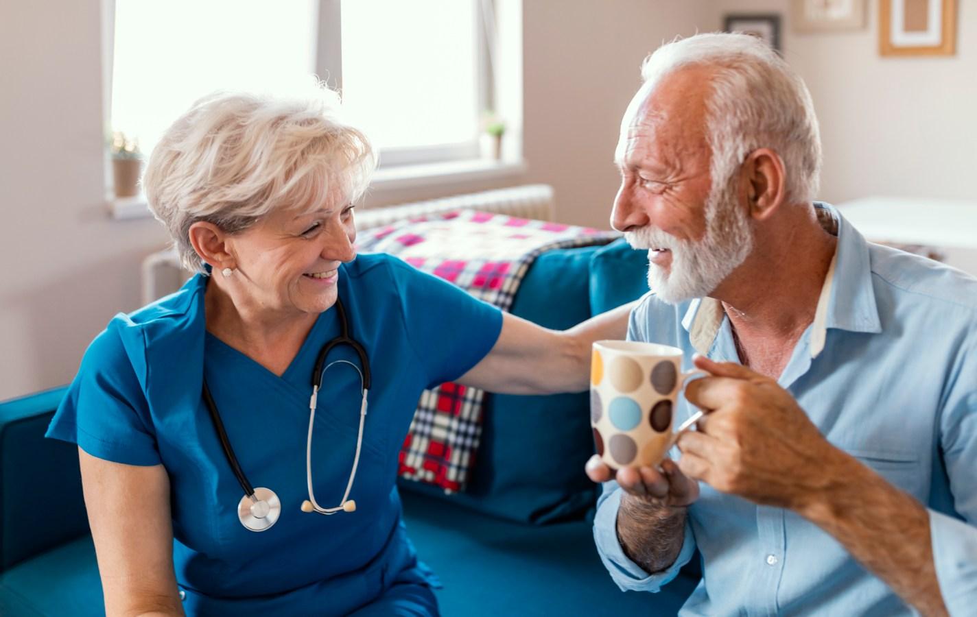 Female caregiver serving afternoon tea to patien