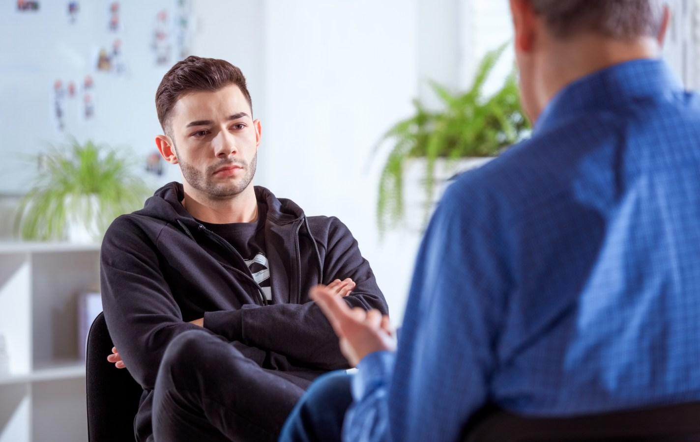 Serious university student listening to therapist