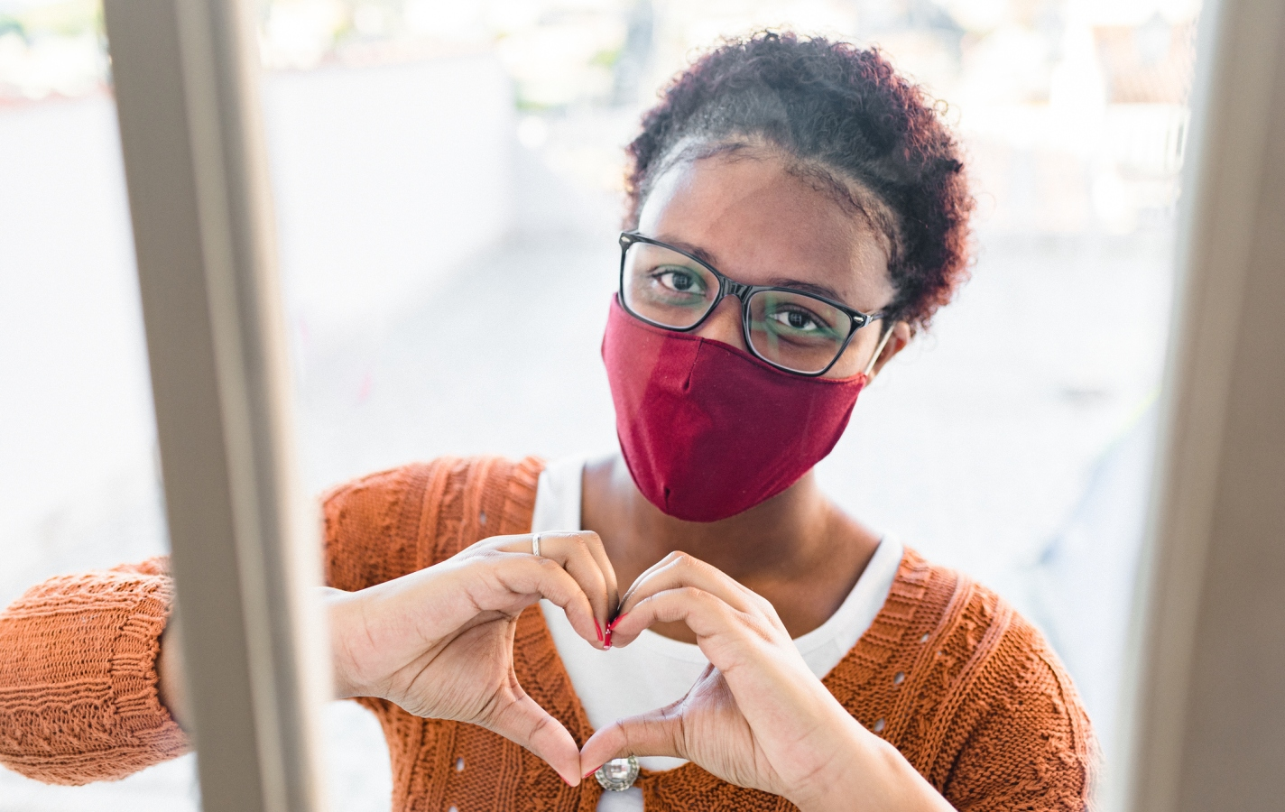 Woman wearing mask and making heart sign through window