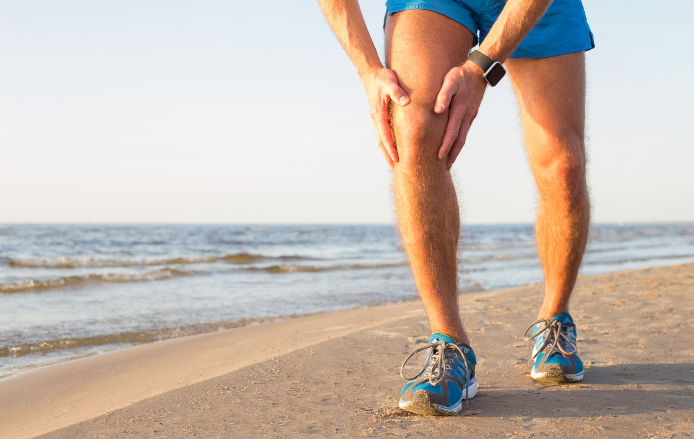 Man running on beach having a pain in his knee