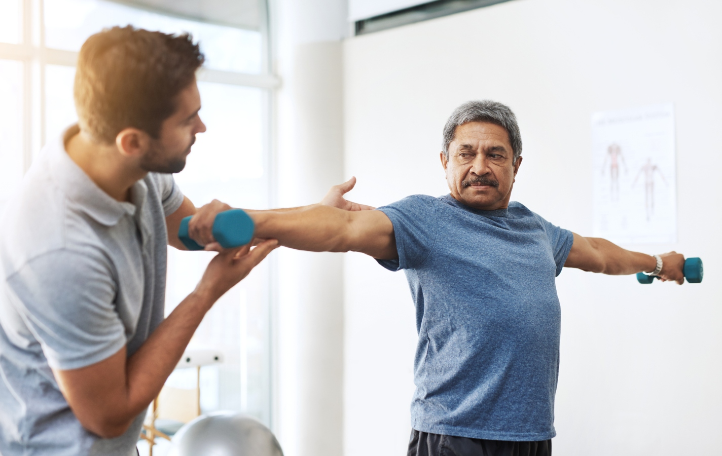 physical therapist working with male patient lifting weights