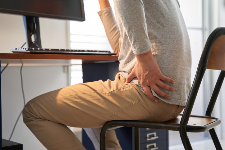 Male businessman who suffers back pain from working from home