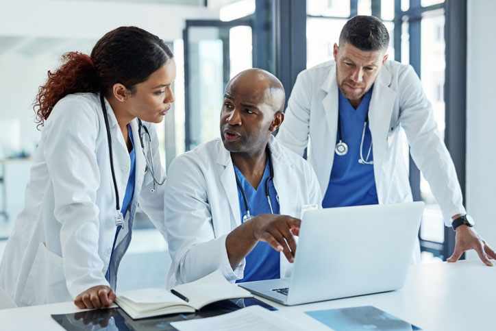 doctors discussing details on laptop - clinical trials