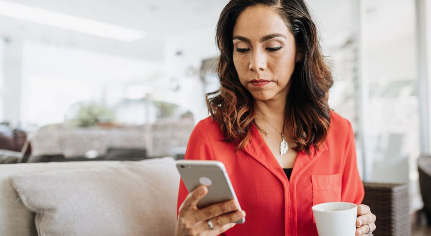 woman sitting on couch with coffee looking at phone