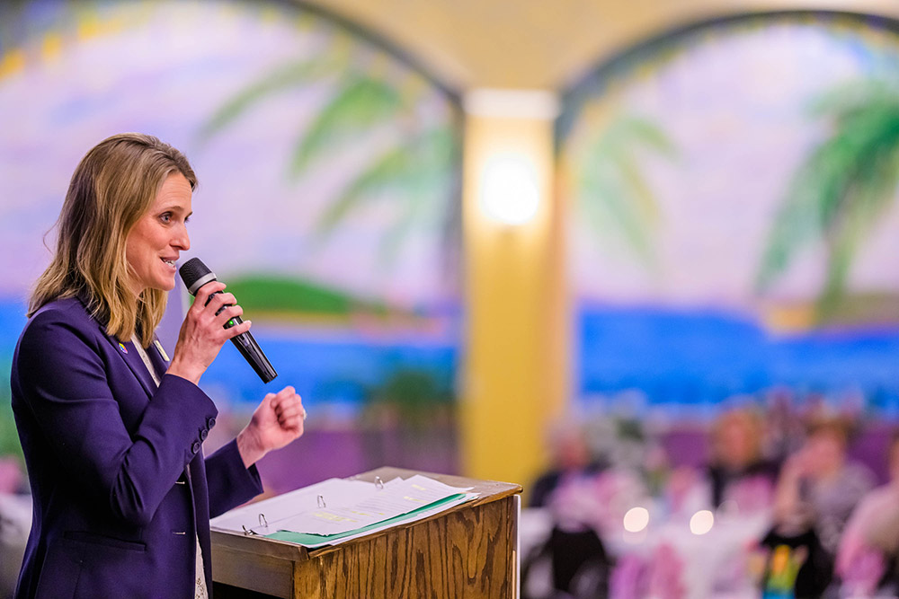 woman speaking at podium with microphone at charity event