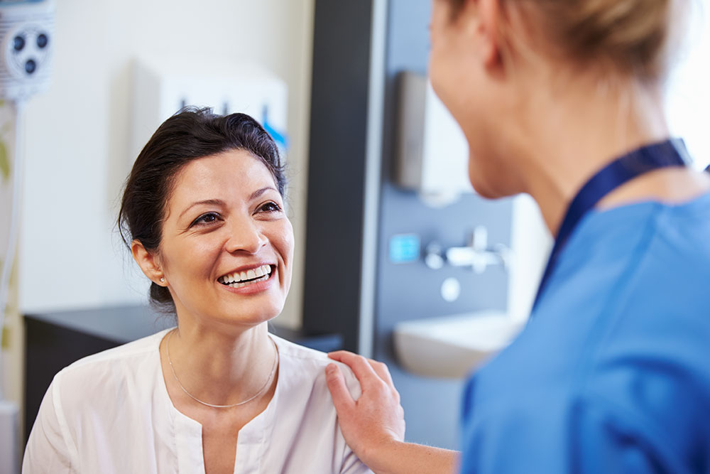 woman smiling talking with doctor