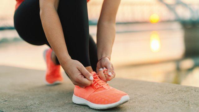 runner kneeling down to tie their shoe