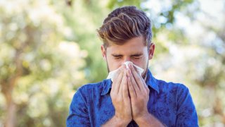 young man with a summer cold blowing his nose