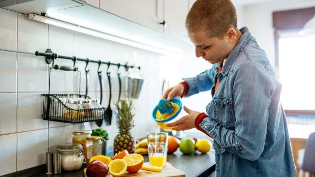 man squeezing fresh orange juice in kitchen