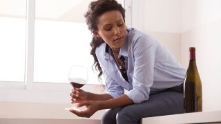 woman drinking a glass of wine looking at bottle