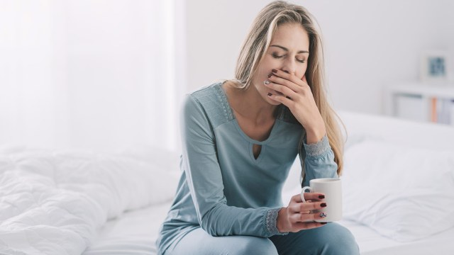 woman yawning while sitting on bed holding cup of coffee