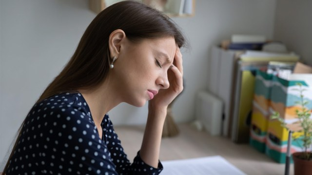 young woman holding her head at office desk
